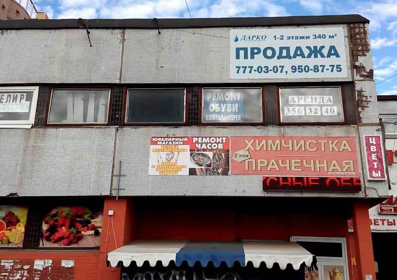 Типичный городской пейзаж. Старые баннеры на грязной стене сливаются в информационное пятно. Читать трудно, смотреть неприятно.